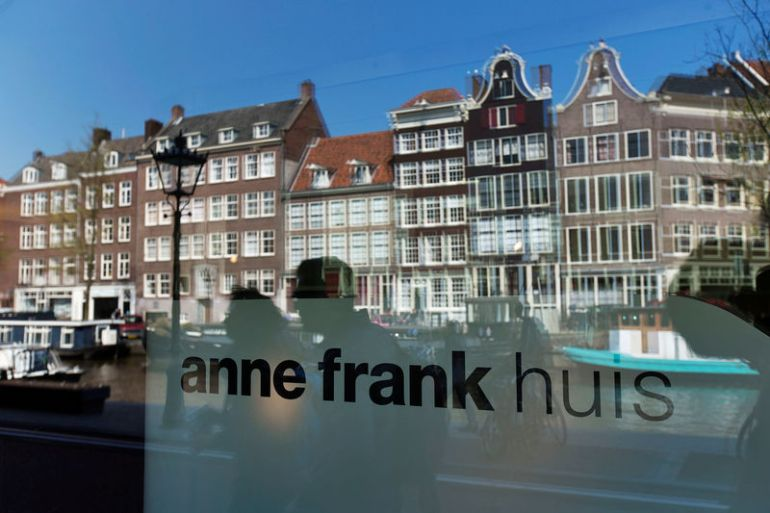 FILE PHOTO: Reflections of tourists and canal houses are seen in the window of the Anne Frank museum in Amsterdam